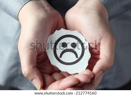 Torn piece of paper with Sad face in the woman's palms. - stock photo