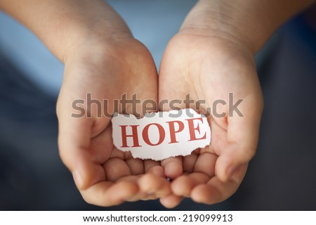 "Torn piece of paper with the word ""Hope"" in the child's palms."