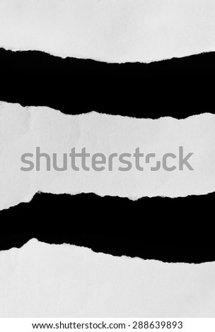 Torn pieces of paper on black background
