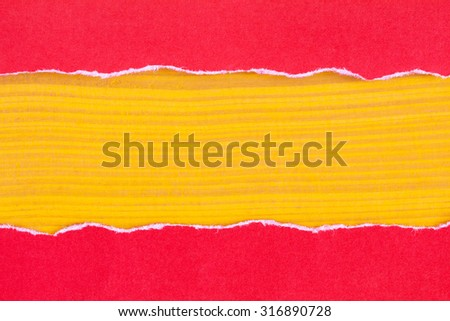 Torn red paper with a yellow wooden background for your text - stock photo