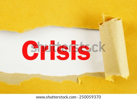 Torn yellow paper with word crisis on white background  - stock photo