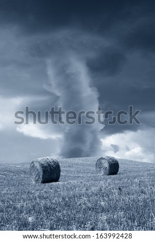 tornado in the country with round bales - stock photo