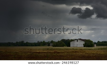 Tornado storm clouds above the shed in the countryside
