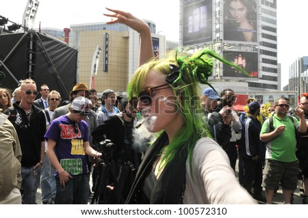 TORONTO - APRIL 20:   A marijuana activist dancing on live music  during the annual marijuana 420 event at Yonge & Dundas Square  on April 20  2012 in Toronto, Canada. - stock photo
