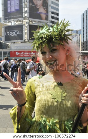 TORONTO - APRIL 20:  A marijuana legalization supporter showing a victory sign during the annual marijuana 420 event at Yonge & Dundas Square  on April 20  2012 in Toronto, Canada. - stock photo