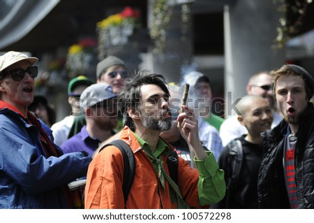 TORONTO - APRIL 20:  Marijuana smokers smoking  in open during the annual marijuana 420 event at Yonge & Dundas Square  on April 20  2012 in Toronto, Canada. - stock photo