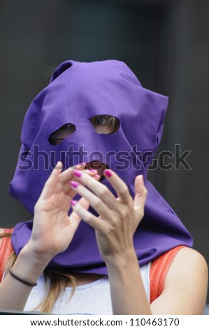 """TORONTO -AUGUST  17:  A Pussy Riot supporter clapping  during a protest rally organized to free """"pussy riot""""on August 17 2012 in Toronto, Canada. - stock photo"""
