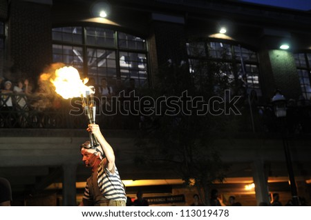 TORONTO-AUGUST 24: A street performer holds a lighted torch during the Buskerfest Festival on August 24, 2012 in Toronto, Canada. - stock photo