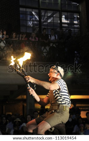TORONTO-AUGUST 24:  A street performer on his colleagues shoulder juggling with fire torches during the Buskerfest Festival on August 24, 2012 in Toronto, Canada. - stock photo