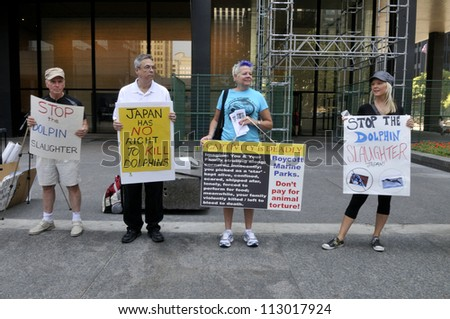 TORONTO-AUGUST 31:Protesters with signs on the sidewalks during a rally to protest the start of the annual  dolphin hunt at Taiji,Japan on August  31, 2012 in Toronto, Canada. - stock photo