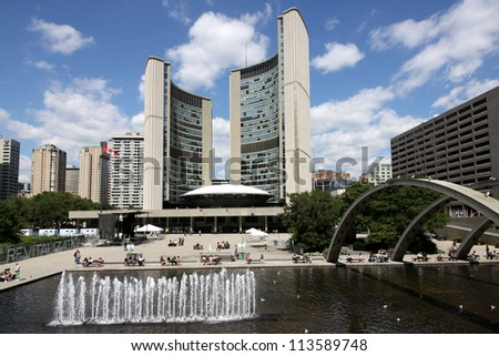 TORONTO - AUGUST 27, 2010:  Toronto's futuristic City Hall has a reflecting pond that is a popular gathering place in summer, on August 27, 2010 in Toronto.