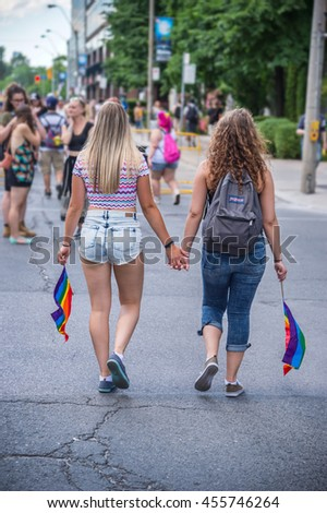 Toronto, CA - 3 July 2016: Two girls holding hands with gay rainbow flags during gay parade - stock photo