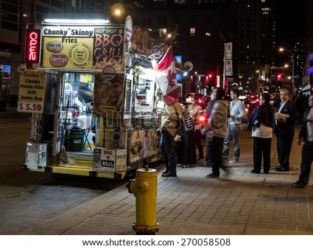 TORONTO, CANADA - APRIL 15, 2015: Food truck along Front Street in downtown Toronto, Canada. Shot at night with customers. - stock photo