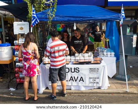 TORONTO, CANADA - 10 AUGUST 2014: A food stall during the Taste of Danforth Street Festival showing people serving and people browsing - stock photo