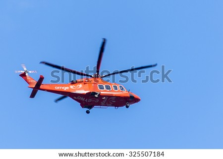TORONTO,CANADA-AUGUST 12,2015: Ornge helicopter on a blue sky background. Ornge is the air ambulance and ground transportation service for the province of Ontario and for the Ministry of Health