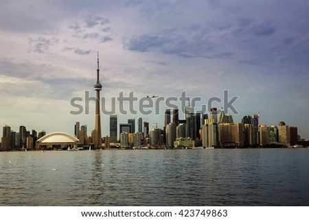 TORONTO, CANADA - AUGUST 25, 2013:  The Toronto skyline, seen from Toronto Island with a passenger jet taking off over the city.