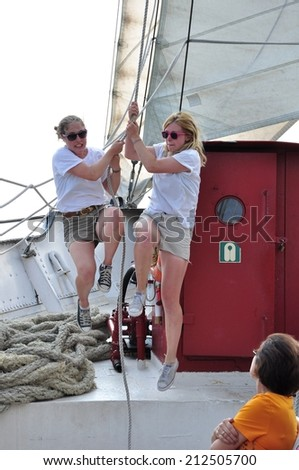 Toronto, Canada - August 2, 2014: Unidentified crews of Kajama ship pull the rope by using their body weights to raise the sail as passenger watch them. - stock photo