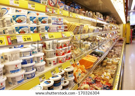 TORONTO, CANADA - DECEMBER 18, 2013: Different brands of cheese on shelves in a grocery store. Hundreds of types of cheese are produced by various countries with different styles, textures and flavors - stock photo