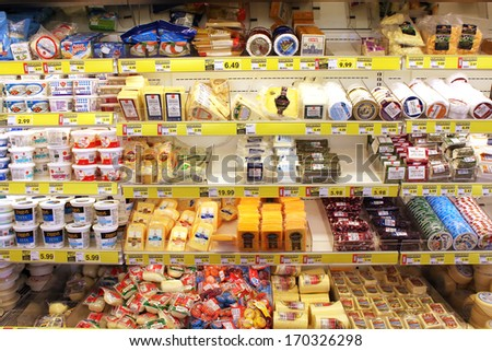 TORONTO, CANADA - DECEMBER 18, 2013: Variety of cheeses on shelves in a grocery store. Hundreds of types of cheese are produced by various countries with different styles, textures and flavors. - stock photo
