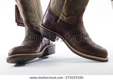 TORONTO, CANADA - FEBRUARY 5, 2016 : Ariat brand of women's leather cowboy boots in an illustrative editorial on bright background