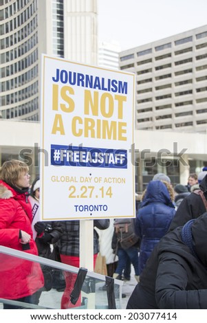 "TORONTO, CANADA - FEBURARY 27 THURSDAY 2014 - Journalist holding banner with ""Journalism is not Crime"" on  Global Day of Action on Feb. 27 in Toronto, Canada."