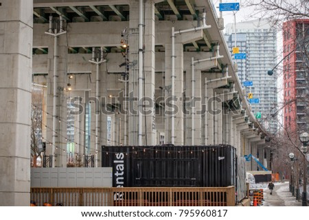 TORONTO, CANADA - JANUARY 9, 2018: LOOKING EAST AT THE GARDINER EXPRESSWAY WITH THE BENTWAY SKATING RINK UNDERNEATH. INDUSTRIAL CRATE WITH RENTALS SIGN ON IT.