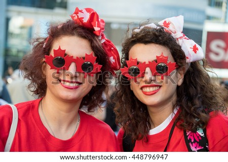 TORONTO,CANADA-JULY 1,2016:Canada Day people: Friends wearing the Canadian colors and enjoying the music in Dundas Square..Canada Day  is the national day of Canada and a federal statutory holiday