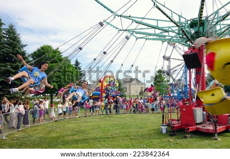 TORONTO, CANADA - JULY 1, 2014: Children enjoying an amusement park ride in Toronto, Canada. - stock photo