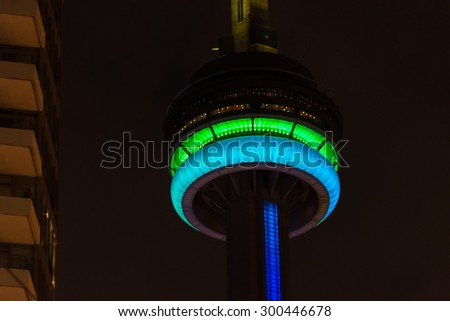 TORONTO,CANADA-JULY 2,2015: CN tower light trials for the Panam games.  The observation deck of the tower glows green and cyan.  Another building can be seen to the left side of the frame. - stock photo