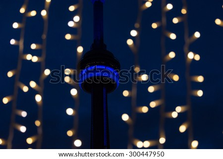 TORONTO,CANADA-JULY 2,2015: CN tower lit blue at dusk with copyspace.  The observation deck of the tower glows blue. The tower is the official PanAm games attraction - stock photo