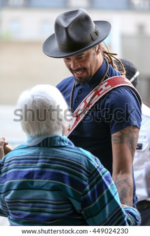 TORONTO, CANADA - JULY 1, 2016: Musician Michael Franti talks to a fan backstage before his TD Jazz Festival concert in Toronto.