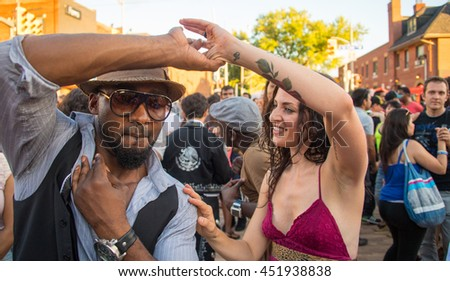 TORONTO,CANADA-JULY 3,2016: Salsa on Saint Clair Avenue West:Couple dancing amongst the multicultural people of Toronto city enjoying the largest Latin Festival in Canada.