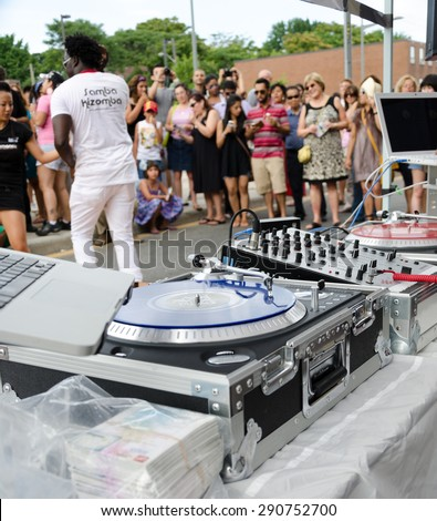 TORONTO,CANADA-JULY 26,2014: Salsa on St. Saint Clair Festival Scenes: A DJ in a Samba Kizomba t-shirt steps away from his equipment . Salsa on St. Clair is a traditional yearly Hispanic festival
