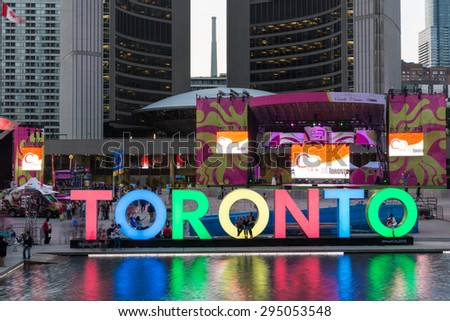 TORONTO,CANADA-JULY 9,2015: The new Toronto sign in Nathan Phillips Square celebrating the PanAm games, the New City Hall at back. Stage have been mounted to held a constant party called Panamania - stock photo