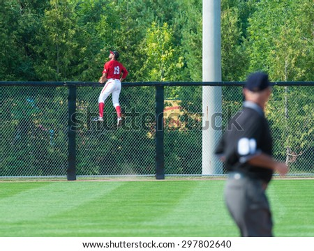 TORONTO,CANADA-JULY 12,2015: Toronto Pan American Games 2015, Baseball tournament: Tyson Gillies goes over a fence trying to catch a home run hit by Colombian team  Case number - 01953074 - stock photo