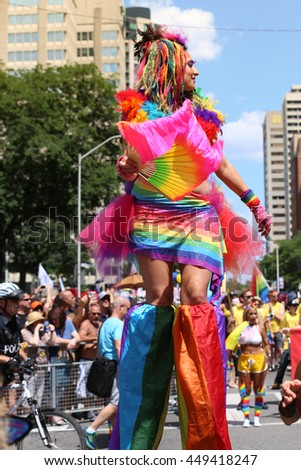 TORONTO, CANADA - JULY 3, 2016: Woman in stilts with balloons marches at Toronto Pride Parade.