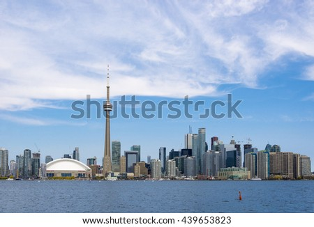 TORONTO,CANADA-JUNE 14,2016: CN tower in Toronto skyline seen from Lake Ontario. The city offers boat tours which are very popular with tourists and visitors to the Financial Capital of Canada