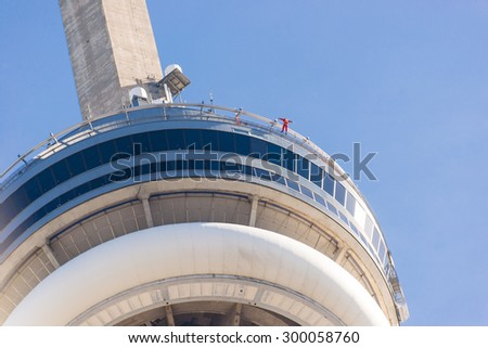 TORONTO,CANADA-JUNE 28,2015:CN tower showing person edgewalking around the edge of the building. EdgeWalk is Toronto newest,tallest urban adventure and the world highest full circle hands-free walk. - stock photo