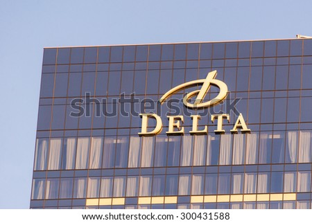 TORONTO,CANADA-JUNE 25,2015: Exterior of the Delta Toronto hotel.  A gray and black glass and steel building rises into a blue sky, with the Delta name and logo in gold at the top. - stock photo