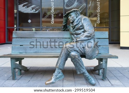 TORONTO,CANADA-JUNE 15,2015: Life-sized bronze statue of Glenn Gould, sitting on a park bench outside the CBC Building in downtown Toronto. - stock photo