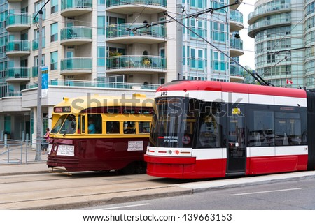 TORONTO,CANADA-JUNE 11,2016: Vintage TTC streetcar next to a modern TTC streetcar. Streetcars are a popular way of transportation and a typical symbol of the Canadian city.