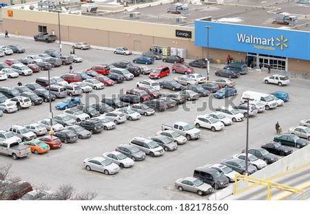 TORONTO, CANADA - MARCH 15, 2014: A parking lot in front of a Walmart store in Toronto, Canada. Walmart has 8,500 stores in 15 countries. Walmart Canada is headquartered in Mississauga, Ontario. - stock photo