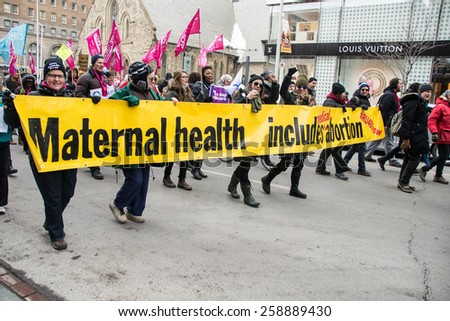 TORONTO,CANADA-MARCH 8,2015: Thousands gathered in Toronto to mark International Women Day IWD with a protest march demanding improvements in many social issues. - stock photo