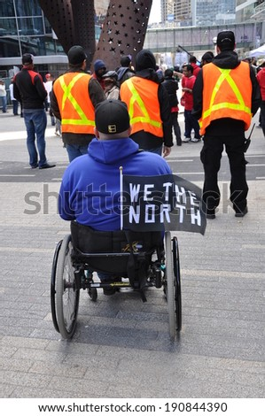 Toronto, Canada - May 4, 2014: A Toronto Raptors fan supports his team at Maple Leaf Square in game 7 of the playoffs  versus Brooklyn Nets. Nets won 104-103.  - stock photo