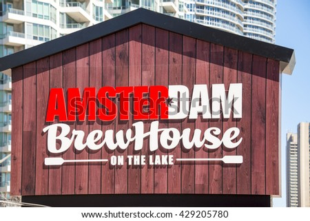 TORONTO,CANADA-MAY 14,2016: Amsterdam Brew House on the Lake, vintage wooden sign. The Brewery is popular for its beer and outdoor's restaurant tables in spring season.