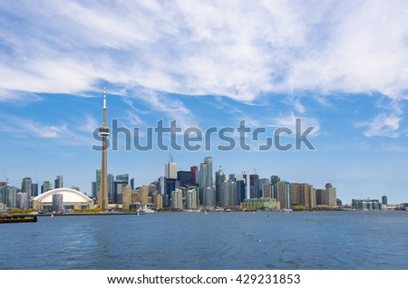 TORONTO,CANADA-MAY 5,2016: CN tower in Toronto skyline seen from Lake Ontario. The city offers boat tours which are very popular with tourists and visitors to the Financial Capital of Canada