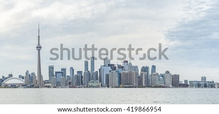TORONTO, CANADA - MAY 12, 2015: Downtown Toronto skyline with the CN Tower , Rogers Centre and financial district skyskrapers just before rain -  panoramic - stock photo