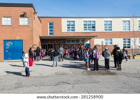 TORONTO,CANADA-MAY 22,2015: Everyday scene outside a public middle school: Parents and students waiting in line to enter building on first day of school, some students crowd together  - stock photo