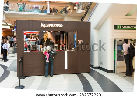TORONTO,CANADA-MAY 15,2015:Nespresso coffee booth in Eaton Centre.Nespresso machines brew espresso from coffee capsules a type of pre-apportioned single-use container of ground coffee and flavorings.  - stock photo