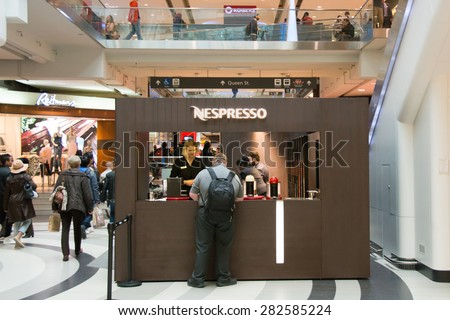 TORONTO,CANADA-MAY 15,2015: Nespresso coffee booth in Eaton Centre.Nespresso machines brew espresso from coffee capsules a type of pre-apportioned single-use container of ground coffee and flavorings - stock photo